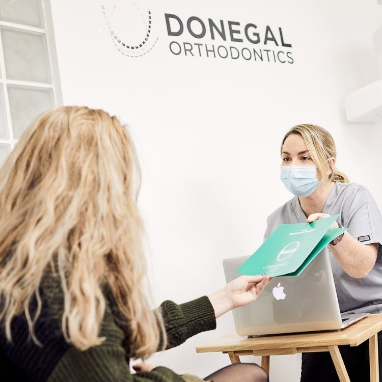 Orthodontic Assistant handing the Invisalign treatment plan to patient at Donegal Orthodontics in Letterkenny
